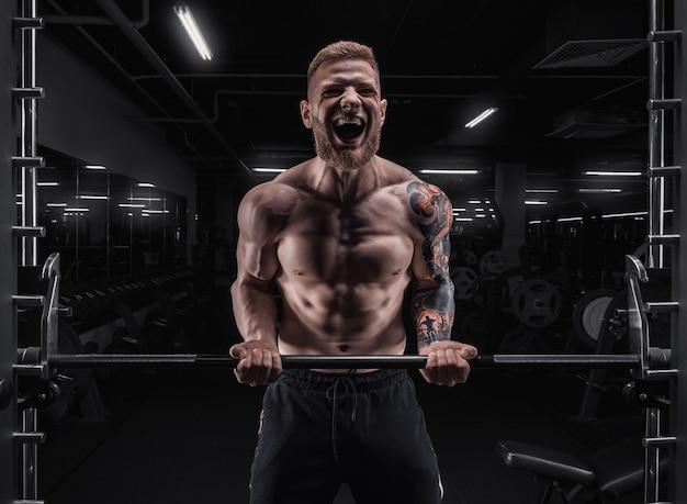 Портрет спортсмена, накачивающего бицепс в тренажерном зале. бодибилдинг и фитнес-концепция. смешанная техника