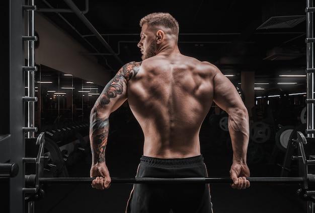 Портрет спортсмена, сидящего на штанге в тренажерном зале. вид со спины. бодибилдинг и фитнес-концепция. смешанная техника