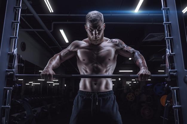 Портрет спортсмена, стоящего перед штангой в тренажерном зале. бодибилдинг и фитнес-концепция. смешанная техника