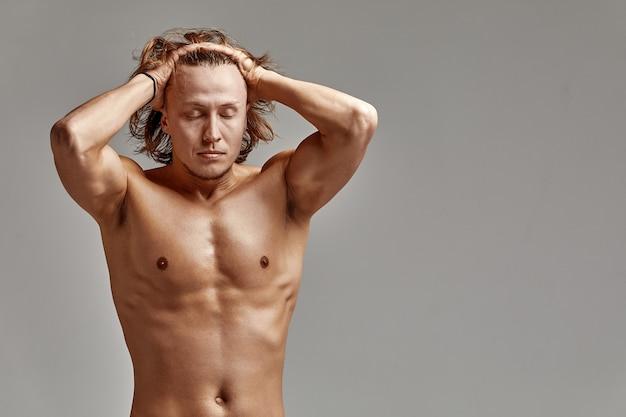 Портрет пловца-спортсмена на сером фоне, в отличной стойкой форме, харизматичный, взрослый, фото редактированное, яркая улыбка, поправляет волосы, серый фон, копии космоса.