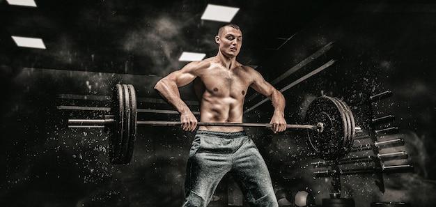 Портрет спортсмена, поднимающего штангу в тренажерном зале. понятие спорта и здорового образа жизни. смешанная техника