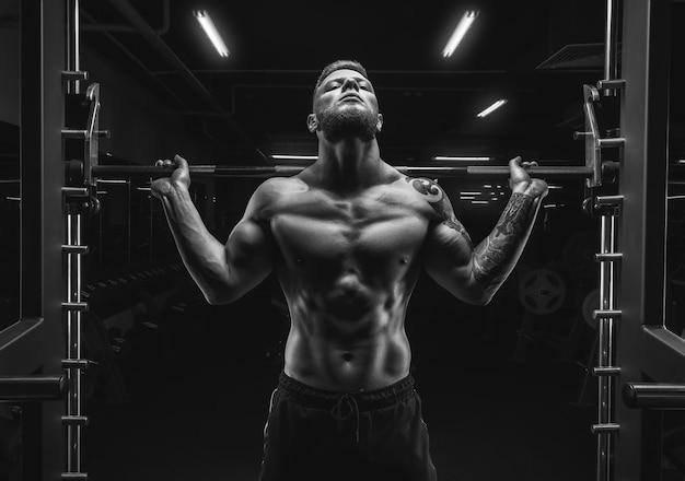 Портрет спортсмена со штангой на плечах спортзала. бодибилдинг и фитнес-концепция. смешанная техника