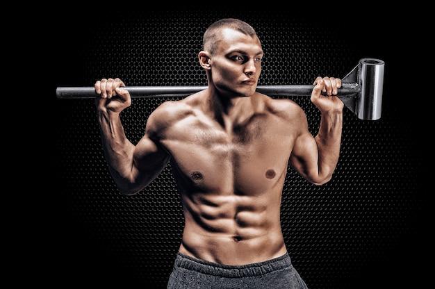 Портрет спортсмена с кувалдой на плечах.