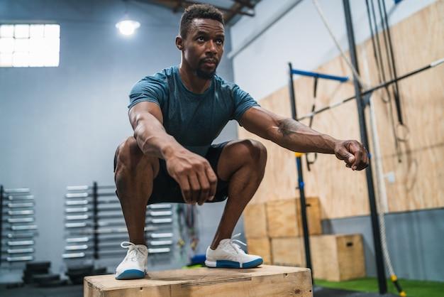 ボックスジャンプ運動を行う運動の男の肖像画。 crossfit、スポーツ、健康的なライフスタイルのコンセプト。