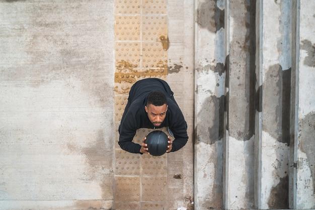屋外でウォールボール運動をしている運動選手の肖像画。スポーツと健康的なコンセプト。
