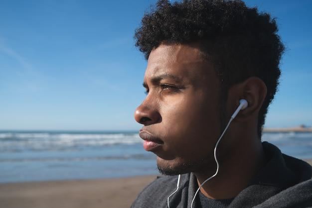 ビーチで運動のために休んでいる間、イヤホンで音楽を聴いている運動選手の肖像画。スポーツと健康的なライフスタイル。