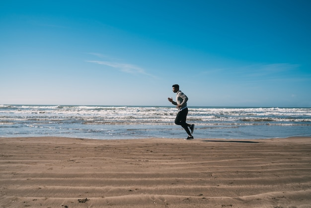 ビーチで走っている運動選手の肖像画。スポーツ、フィットネス、健康的なライフスタイル。