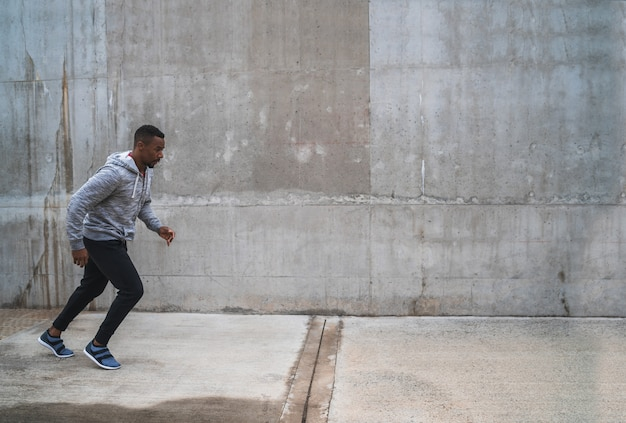 灰色の背景に対して通りを走っている運動選手の肖像画。スポーツと健康的なライフスタイル。