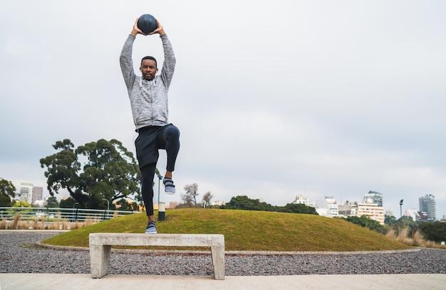 屋外の公園で薬のボールでトレーニングしている運動選手の肖像画。スポーツと健康的なコンセプト。