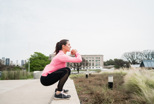 屋外の公園で運動をしている運動女性の肖像画。スポーツと健康的なライフスタイルのコンセプト。