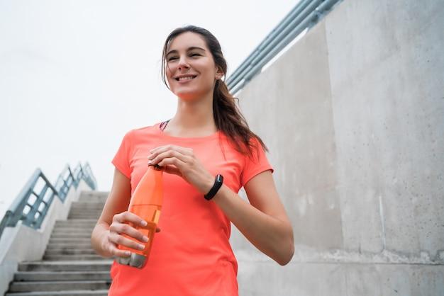 トレーニング後の水を飲む運動女性の肖像画。スポーツと健康のライフスタイルの概念。