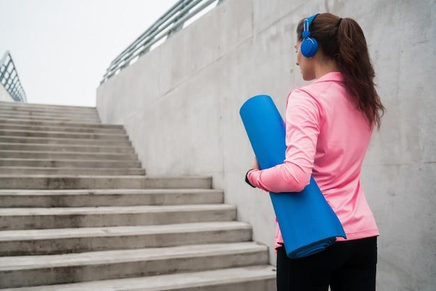音楽を聴きながらトレーニングマットを保持している運動女性の肖像画。スポーツとライフスタイルのコンセプト。
