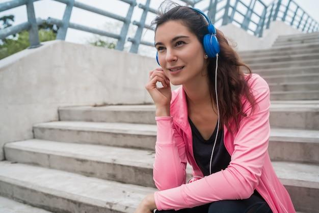 階段に座ってトレーニングの休憩中に音楽を聴いている運動女性の肖像画。スポーツと健康のライフスタイルの概念。