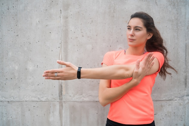야외에서 운동하기 전에 그녀의 팔을 스트레칭 운동 여자의 초상화. 스포츠와 건강한 라이프 스타일.