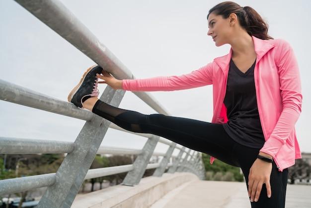 야외에서 운동을하기 전에 다리를 스트레칭 운동 여자의 초상화. 스포츠와 건강한 라이프 스타일.