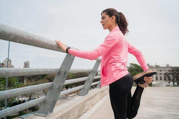 Портрет спортивной женщины, протягивающей ноги перед тренировкой на открытом воздухе. спорт и здоровый образ жизни.