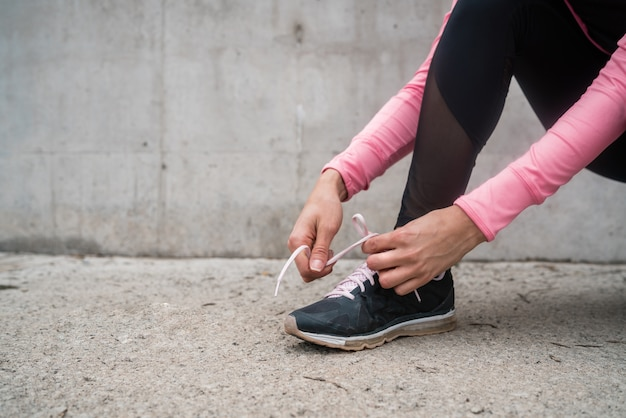 彼女の靴ひもを結び、屋外でジョギングの準備をしている運動女性の肖像画。スポーツと健康的なライフスタイルのコンセプト。