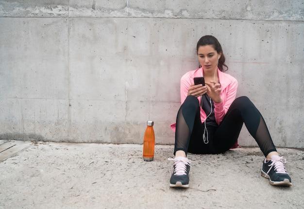 灰色の背景に対してトレーニングの休憩中に彼女の携帯電話を使用して運動女性の肖像画。スポーツと健康のライフスタイル。