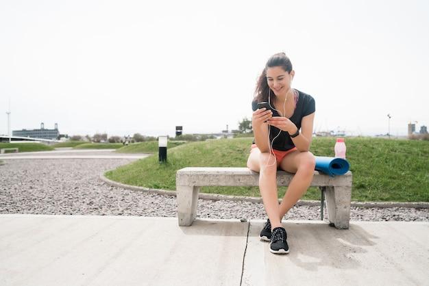 トレーニングの休憩時間に携帯電話を使用している運動女性の肖像画。スポーツと健康のライフスタイル。