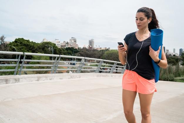 音楽を聴きながらトレーニングマットを持って通りを歩いている運動女性の肖像画。スポーツとライフスタイルのコンセプト。