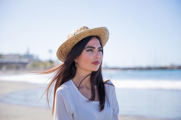 ビーチで魅力的で自信を持って白人の女の子の肖像画。彼女はリラックスして夏用帽子をかぶっています