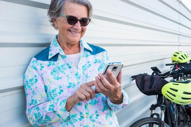 흰색 금속 벽에 기대어 서서 휴대전화로 메시지를 주고받는 매력적이고 웃는 수석 여성의 초상화. 그녀와 가까운 두 개의 전기 자전거 검은 색