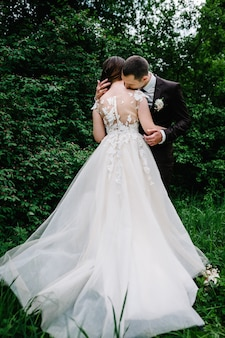 Портрет невесты привлекательной спиной, которая обнимает и целует жениха. свадебная церемония. молодожены венчаются в лесу.