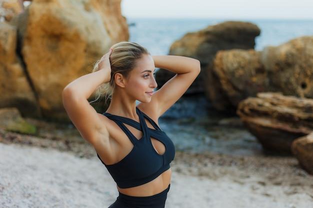 野生のビーチでスポーツウェアの魅力的なブロンドの女性の肖像画。屋外トレーニング