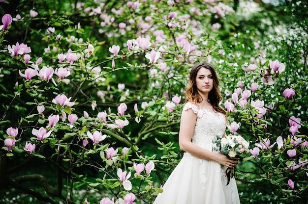 Портрет привлекательной невесты со свадебным букетом на фоне фиолетовых цветов магнолии и зелени. природа. на открытом воздухе. смотрит в камеру. верхняя половина длины.