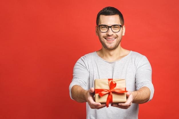 プレゼントボックスを与え、赤い背景で隔離のカメラを見ている魅力的なカジュアルな男の肖像画