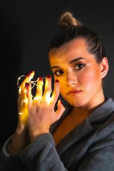 Портрет привлекательной кавказской женщины с гирляндами на руках