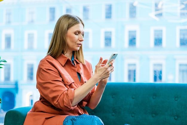 소파에 앉아 셀카 자유 시간을 즐기는 매력적인 쾌활한 여성 블로거의 초상화...