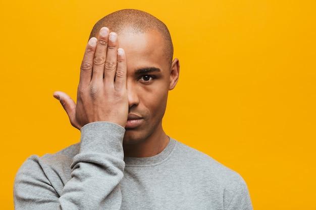 Портрет привлекательного, уверенного в себе случайного молодого африканца, стоящего над желтой стеной, закрывает глаза