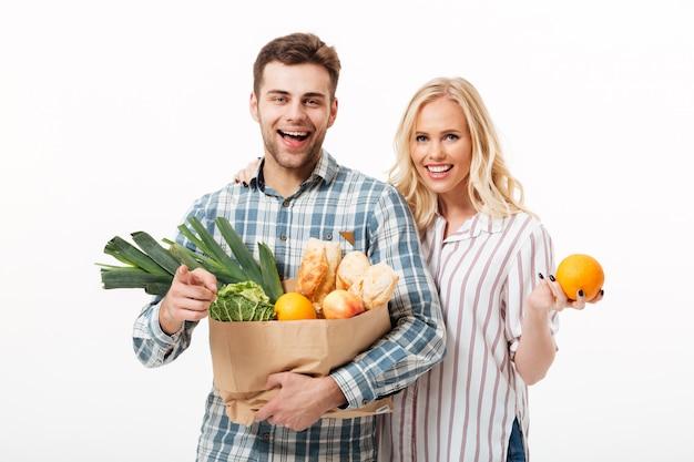 Портрет привлекательной пары держа бумажную хозяйственную сумку