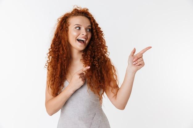 Портрет привлекательной возбужденной молодой женщины с длинными вьющимися рыжими волосами, стоя изолированно, представляя пространство для копирования, указывая
