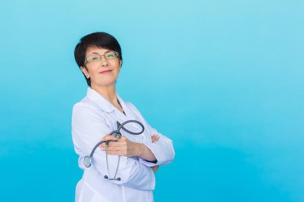 복사 공간이 있는 파란색 위에 흰색 코트를 입은 매력적인 여성 의사의 초상화
