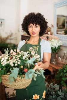 Портрет привлекательный женский флорист, холдинг корзины цветов