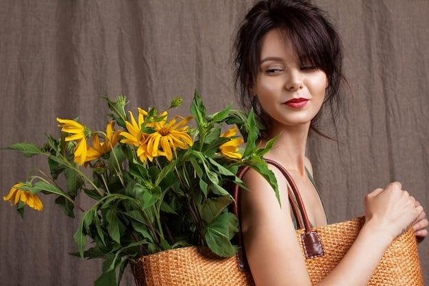 魅力的な女の子とバッグの中の黄色い花の大きな束の肖像画