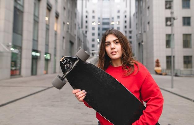Портрет привлекательная девушка в красной толстовке стоит с коньком в руках на фоне современного города и смотрит в камеру. девушка с лонгбордом на улицах города.