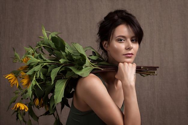 黄色い花の大きな束を持つ魅力的な女の子の肖像画