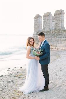 Портрет привлекательного groom смотря невесту на природе около озера garda в sirmione, италии. свадебная церемония возле озера. счастливый и радостный момент.