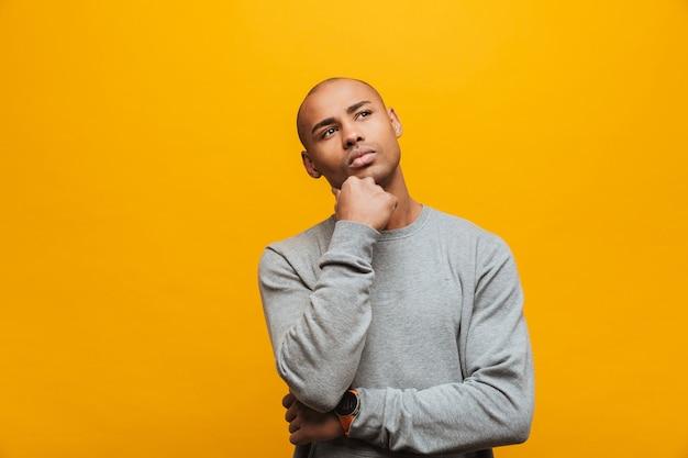 노란 벽 위에 서 있는 매력적인 수심에 찬 캐주얼 젊은 아프리카 남자의 초상화