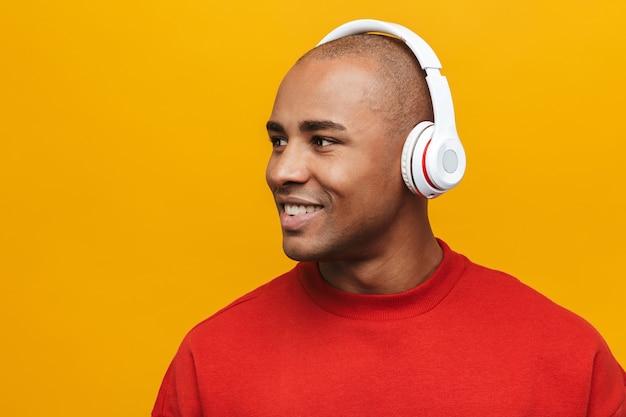 Портрет привлекательного улыбающегося уверенного в себе молодого африканца, стоящего над желтой стеной, слушающего музыку в беспроводных наушниках и смотрящего в сторону