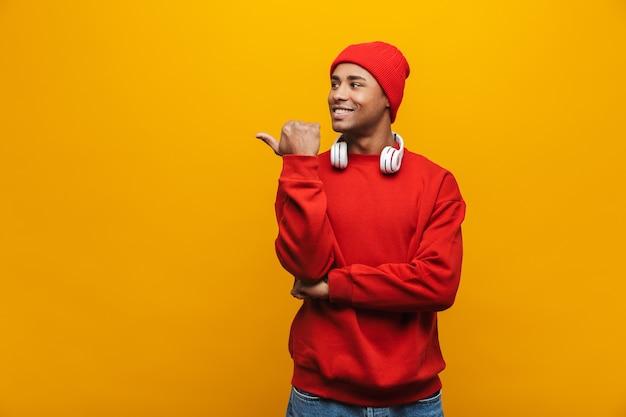 Портрет привлекательного улыбающегося уверенного в себе случайного молодого африканца, стоящего над желтой стеной и указывающего пальцем на пространство для копирования Premium Фотографии