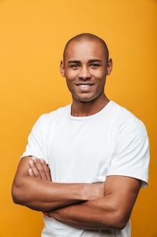 黄色の壁の上に立っている魅力的な笑顔の自信を持ってカジュアルな若いアフリカ人の肖像画