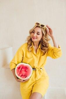 노란색 여름 양복과 여름 선글라스를 쓴 매력적인 웃는 여성의 초상화와 손에 즙이 많은 수박이 있습니다. 행복한 여름, 휴가, 영감. 부드러운 선택적 초점입니다.