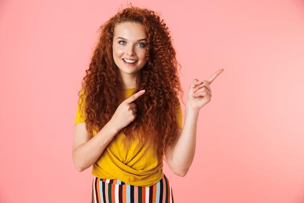 Портрет привлекательной улыбающейся молодой женщины с длинными вьющимися рыжими волосами, стоящей изолированно, представляя пространство для копирования