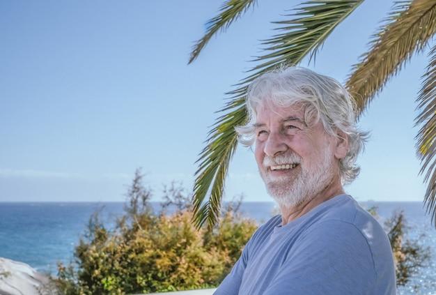 Портрет привлекательного седовласого старшего мужчины на открытом воздухе у моря, стоящего в тени дерева