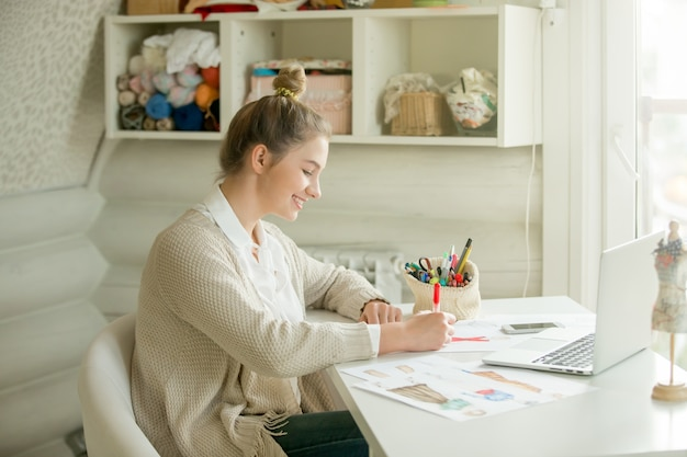 의류 디자인을 색칠하는 매력적인 여자의 초상화
