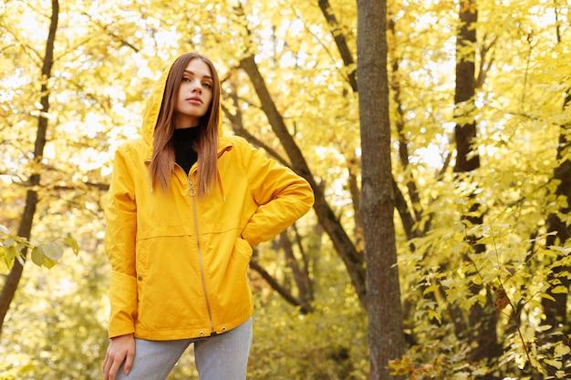 가 노란 나무 앞 노란 비옷에 매력적인 여자의 초상화. 오른쪽에 텍스트를 위한 여유 공간. 가을